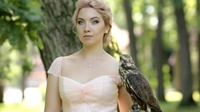 vídeos y material grabado en eventos de stock de mujer rubia de misterio con un halcón en el brazo en el bosque de niebla - descripción física