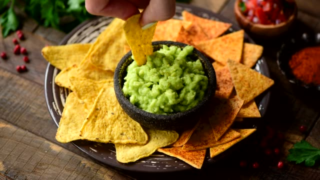 Nacho corn tortilla chips and guacamole sauce Nacho corn tortilla chips and guacamole sauce. Hand dipping chip into avocado sauce. Tex mex food, healthy vegan appetizer concept avocado stock videos & royalty-free footage