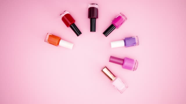 Nail polishes and manicure accessories appear on pastel pink background - Stop motion