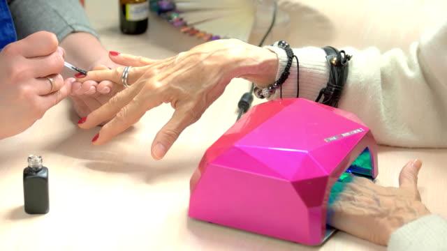 vidéos et rushes de technicien faire manucure des ongles. - ongle