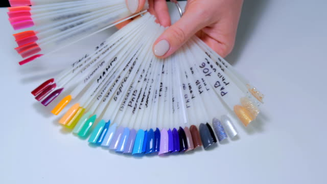 Nail technician shows the color palette of nail services in beauty salon. video