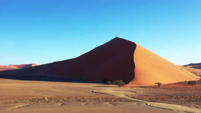 Nambia Desert Sand Dune Sossusvlei Drone 4K Video Video 4K drone flight towards in warm late afternoon light close to sunset towards the desert sand dune 40 in the Namib-Naukluft National Park. Dune 40 is the highest star dune in Sossusvlei, Namibia.. Sesriem, Namib-Naukluft National Park, Namibia, South West Africa. swakopmund stock videos & royalty-free footage