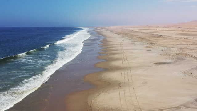 Namibia Swakopmund Langstrand Beach Walvis Bay Drone Video Flight I Langstrand Beach Aerial Drone 4K Video Real Time Flight along Atlantic Ocean Sea and Sand Coast - Skeleton Coast between Swakopmund and Walvis Bay. The endless South Atlantic Ocean Beach Coast of Namibia close to Swakopmund with Skid Marks from 4x4 Cars . National Road B2 with Trucks and Cars driving in the background horizon. Skeleton Coast, Swakopmund - Walvis Bay, Erongo Region, Namibia, Africa. swakopmund stock videos & royalty-free footage