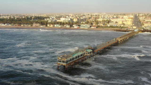 Namibia Swakopmund Waterfront Jetty Drone Sunset Flight By 4K Video Swakopmund Waterfront Jetty. Aerial 4K Drone Video Flight along the waterfront beach passing the famous Swakopmund Jetty Bridge - Pier of Swakopmund in Sunset Light. Flight over the South Atlantic Ocean. Aerial Drone Point of View 4K Video, South Atlantic Ocean, Swakopmund, Erongo Region, Namibia, Africa swakopmund stock videos & royalty-free footage