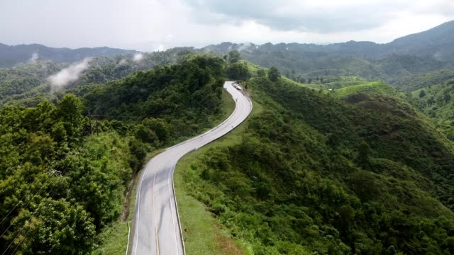 nan, thailand. aerial view of beautiful sky road over top of mountains with green jungle. road trip on curve road in mountain. - passo montano video stock e b–roll