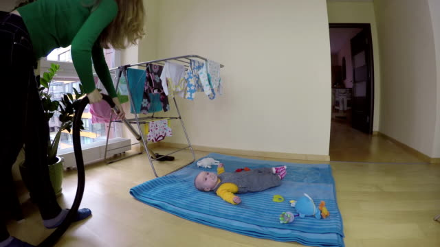 nanny look after baby daughter and clean home with hoover. video
