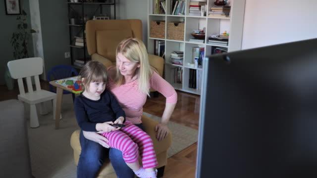 dadı 3 yaşındaki kız ile evde tv izlerken - ultra yüksek çözünürlüklü televizon stok videoları ve detay görüntü çekimi