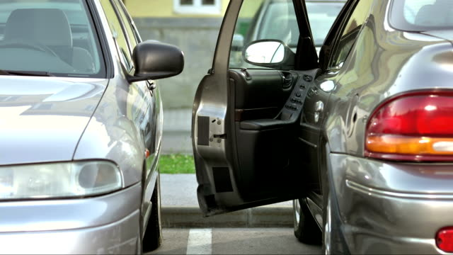 MS Narrow Parking Space HD1080p: MEDIUM shot of a woman having a problem to getting out of her car she parked in a narrow parking space. negative emotion stock videos & royalty-free footage