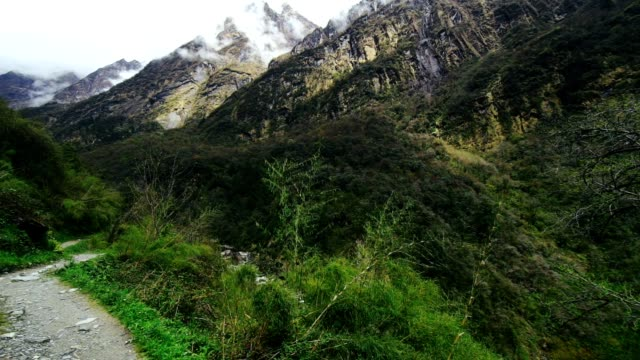 Narrow path with steep cliff among high mountains misty haze and green forest video