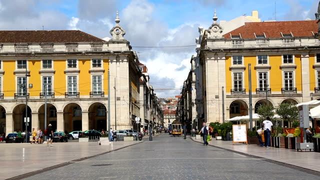 vídeos de stock e filmes b-roll de narrow street between two buildings in downtown of lisbon, tourist taking photo - eletrico lisboa