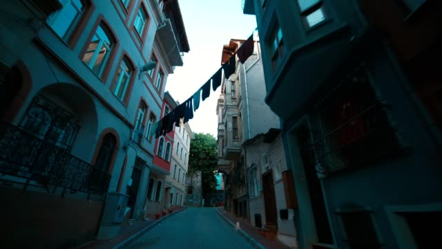 vídeos de stock e filmes b-roll de narrow streets of old istanbul, colorful clothes hanging on clothesline between buildings' windows - isolated house, exterior