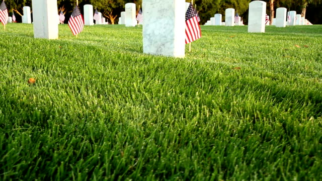 US National Cemetery Dolly camera moves down past a marble tombstone at a US National Cemetery. Many more tombstones can be seen in the background. Small flags are placed next to each tombstone. memorial day stock videos & royalty-free footage
