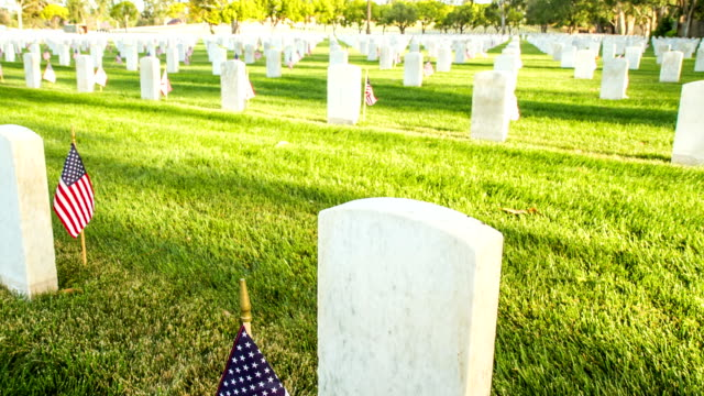 US National Cemetery Dolly camera moves up past a marble tombstone at a US National Cemetery. Many more tombstones can be seen in the background. Small flags are placed next to each tombstone. memorial day stock videos & royalty-free footage