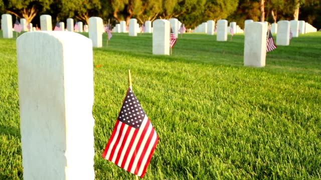 US National Cemetery Camera moves up past a marble tombstone at a US National Cemetery. Many more tombstones can be seen in the background. Small flags are placed next to each tombstone. memorial day stock videos & royalty-free footage