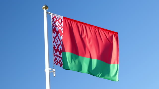 national flag of the republic of belarus Close-up view flag republic of belarus waving in the wind on a blue sky background without clouds, two horizontal stripes of red and green color with traditional Belarusian pattern belarus stock videos & royalty-free footage