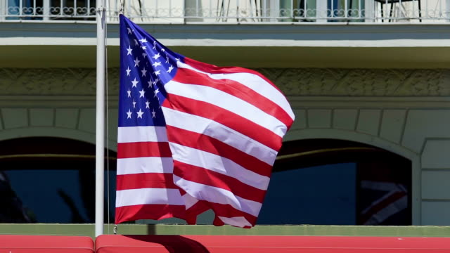 National flag of United States of America flying in wind, rising above embassy video
