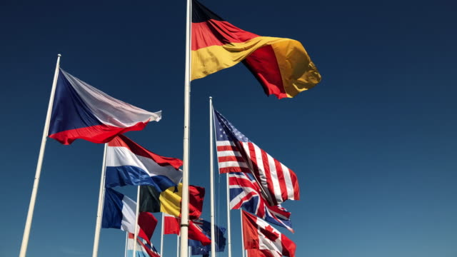 national flags together flying in slow motion on blue sky background - bandiera nazionale video stock e b–roll