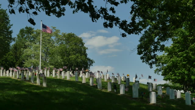 national veterans cemetery with blowing flag 4k - memorial day stock videos and b-roll footage