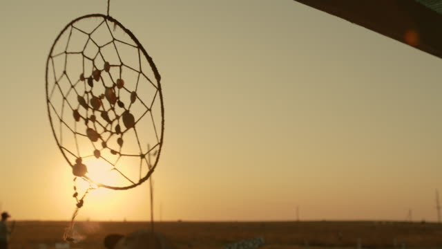 Native American dreamcatcher hanging in breeze at sunset