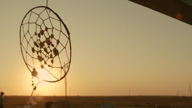 acchiappasogni dei nativi americani appeso nella brezza al tramonto - hippy video stock e b–roll