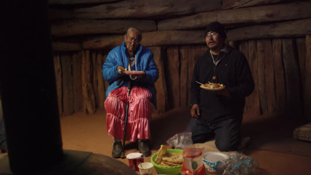 A Native American Man (Navajo) in His Forties Kneels on the Floor of a Hogan (Navajo Hut) Eating Food and Talking with Others as He Sits Next to an Elderly Woman Also Eating A Native American Man (Navajo) in His Forties Kneels on the Floor of a Hogan (Navajo Hut) Eating Food and Talking with Others as He Sits Next to an Elderly Woman Also Eating minority groups stock videos & royalty-free footage