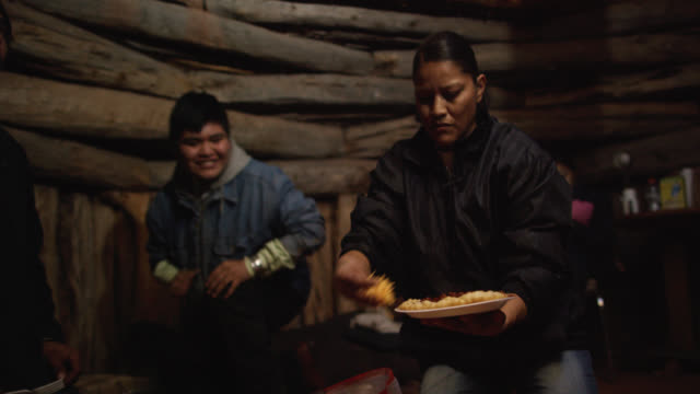 Native American (Navajo) People of Various Ages Talk, Laugh, and Prepare Food Together in a Wooden Hogan (Navajo Hut)