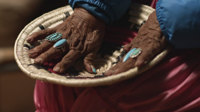 A Native American Woman (Navajo) in Her Eighties Wearing Turquoise Rings on Her Fingers Touches and Looks at a Woven Navajo Basket