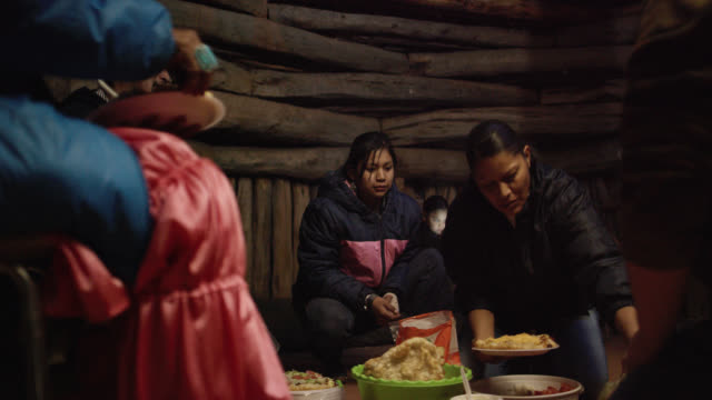 A Native American (Navajo) Woman in Her Forties Prepares a Plate of Food for a Teenaged Girl in a Wooden Hogan (Navajo Hut)