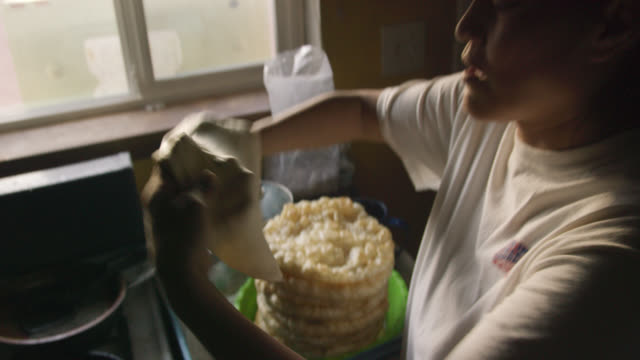 A Native American (Navajo) Woman in Her Forties Uses Her Hands to Form a Tortilla (Fry Bread) and Then Places It into a Pan of Oil for Cooking on a Stovetop in a Kitchen
