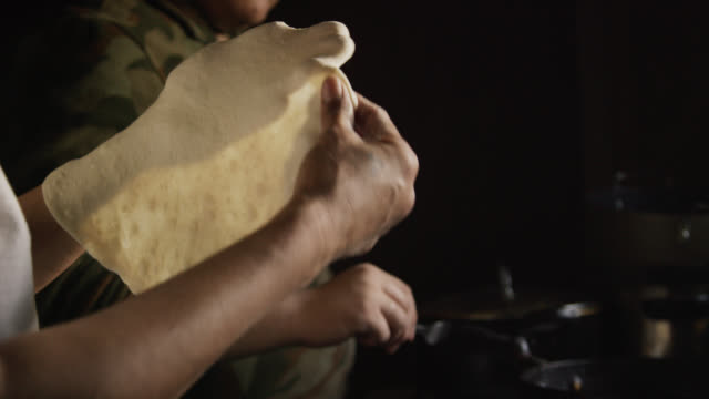 A Native American (Navajo) Woman's Hands Form a Raw Tortilla (Fry Bread) while Another Woman Removes a Cooked Tortilla and Places It on a Finished Stack before Placing a Raw Tortilla into Oil on a Stove Indoors