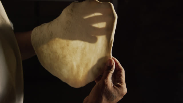 A Native American (Navajo) Woman's Hands Form a Tortilla (Fry Bread) before Placing It into a Pan of Oil on a Stovetop in a Kitchen
