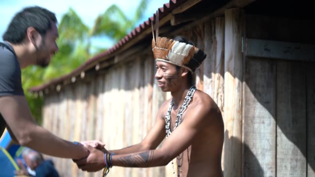 native brazilian welcoming the tourist on brazilian indigenous tribe, from guarani ethnicity - этническая группа стоковые видео и кадры b-roll
