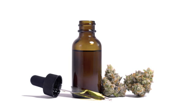 Natural Alternative Medicine Marijuana CBD Oil on White Motion background Simple cannabis liquid display in bright lightbox slowly rotating with glass jar droppper by weed buds cannabidiol stock videos & royalty-free footage