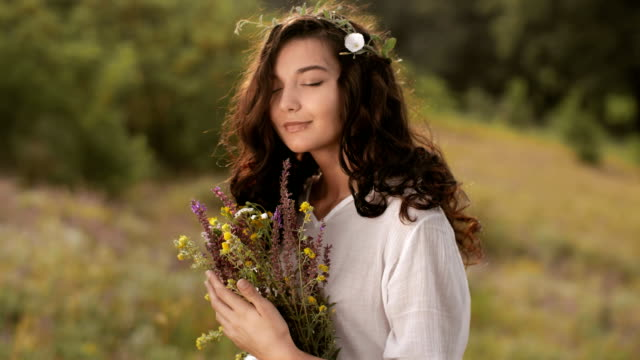 Natural beauty girl with bouquet of flowers outdoor in freedom enjoyment concept. Focus on flowers
