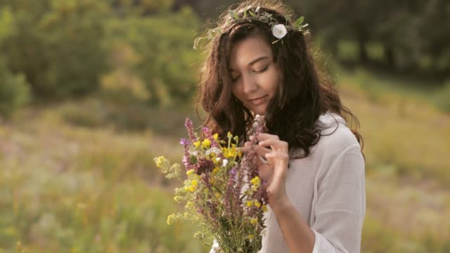Natural beauty girl with bouquet of flowers outdoor in freedom enjoyment concept. Portrait photo