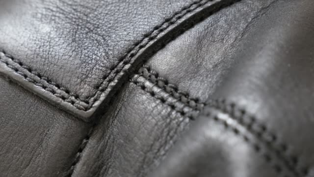 natural dark leather texture with stitches close-up 4k 2160p 30fps uhd tilting footage - slow tilt over manufactured leather fabric for jacket or shooes 4k 3840x2160 ultrahd video - cucitura video stock e b–roll