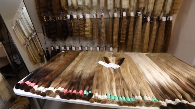 doğal kadın saçı, güzel kadın saçı. salonda uzun saç uzantıları - peruk stok videoları ve detay görüntü çekimi