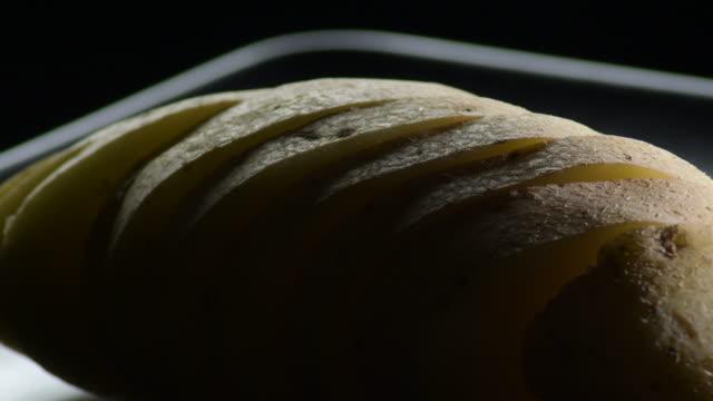 natural potato cut gyrating on a black tray. solanum tuberosum - group of people filmów i materiałów b-roll