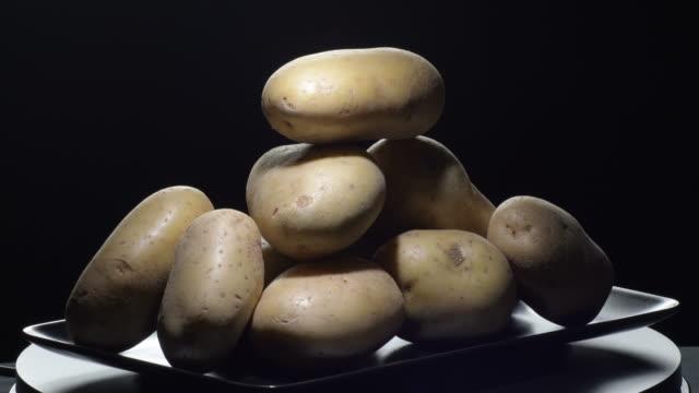 natural potatoes gyrating on a black tray. solanum tuberosum - group of people filmów i materiałów b-roll
