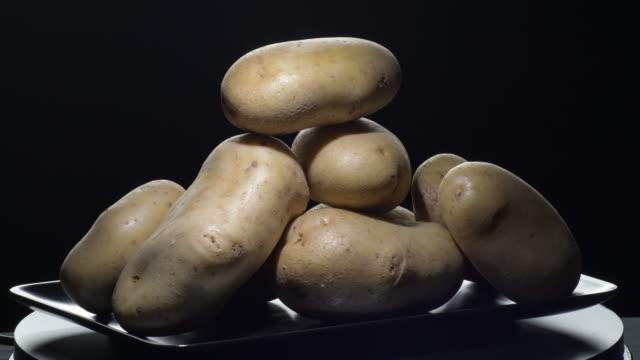 natural potatoes vegetables gyrating on a black tray. solanum tuberosum - group of people filmów i materiałów b-roll