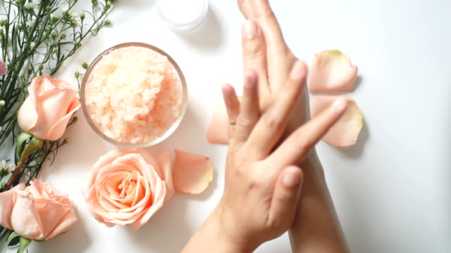 4K. natural skincare concept. woman apply white cream on her hands on white background with jar of cosmetic cream, salt spa scrub ,rose and  white flowers with copy space