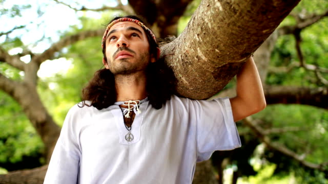Nature boy A young man embraces the nature. Hippie style young man makes a silent protest. Prime Lens used for selective focus. FULL HD 30p. Alternative shots in portfolio, please visit. hippie stock videos & royalty-free footage