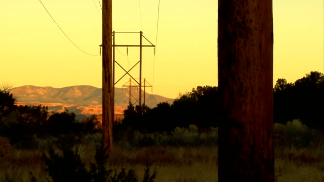 Nature vs.Technology - Powerlines & Mountains Yellow morning light illuminates wooden powerpoles and electric lines set against a New Mexico mountain background power supply stock videos & royalty-free footage