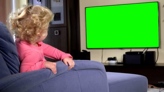 vídeos de stock e filmes b-roll de naughty girl watching tv sitting on sofa. green chroma key screen - tv e familia e ecrã