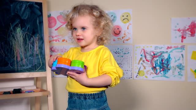 stockvideo's en b-roll-footage met ondeugende gelukkige kind gooien haar speelgoed thuis - blond curly hair