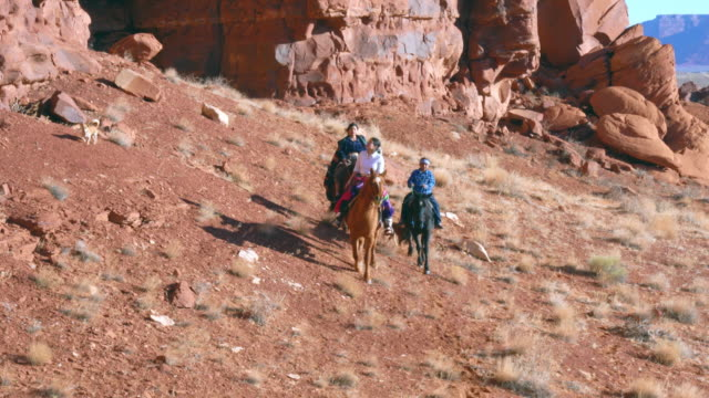 Navajo Brother And Sisters Riding Horses Around The Large Rock Formations On Their Land
