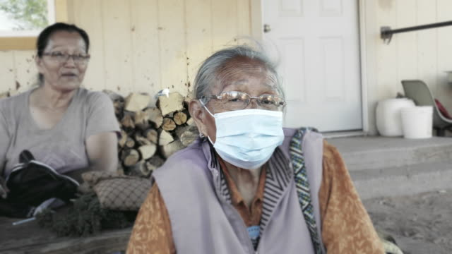 Navajo Grandma in her 80s sitting in front of her house in Monument Valley Arizona wearing a face mask to prevent contracting the Corona or Covid-19 Virus Navajo Grandma in her 80s sitting in front of her house in Monument Valley Arizona wearing a face mask to prevent contracting the Corona or Covid-19 Virus indian family stock videos & royalty-free footage