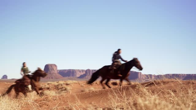 Navajo siblings riding on horses in Monument Valley Arizona