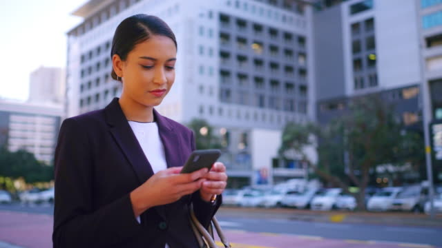 Navigating the world of business with pocket technology 4k video footage of a young businesswoman using a smartphone while walking through the city surfing the net stock videos & royalty-free footage