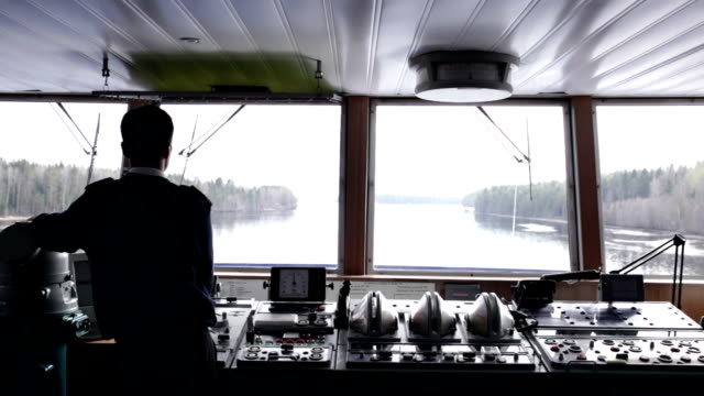 Navigation officer driving ship on the river. video